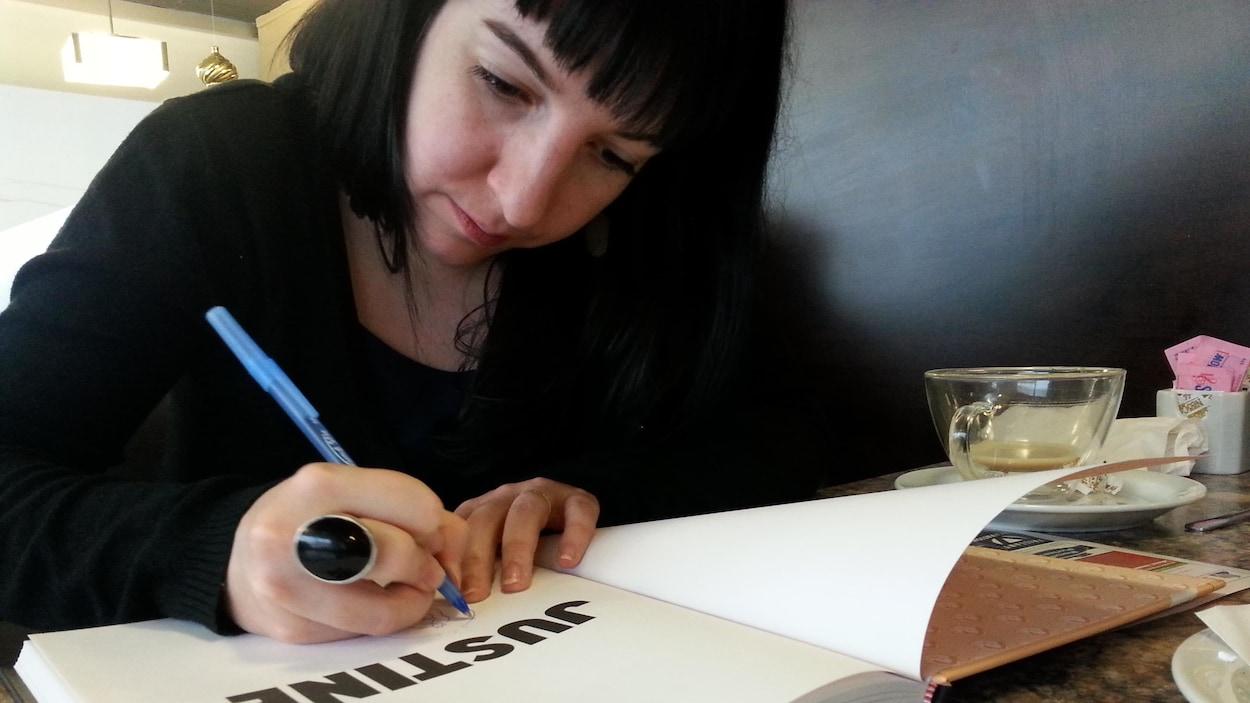 La bédéiste Iris en train de dédicacer un ouvrage en étant assise à une table d'un café.