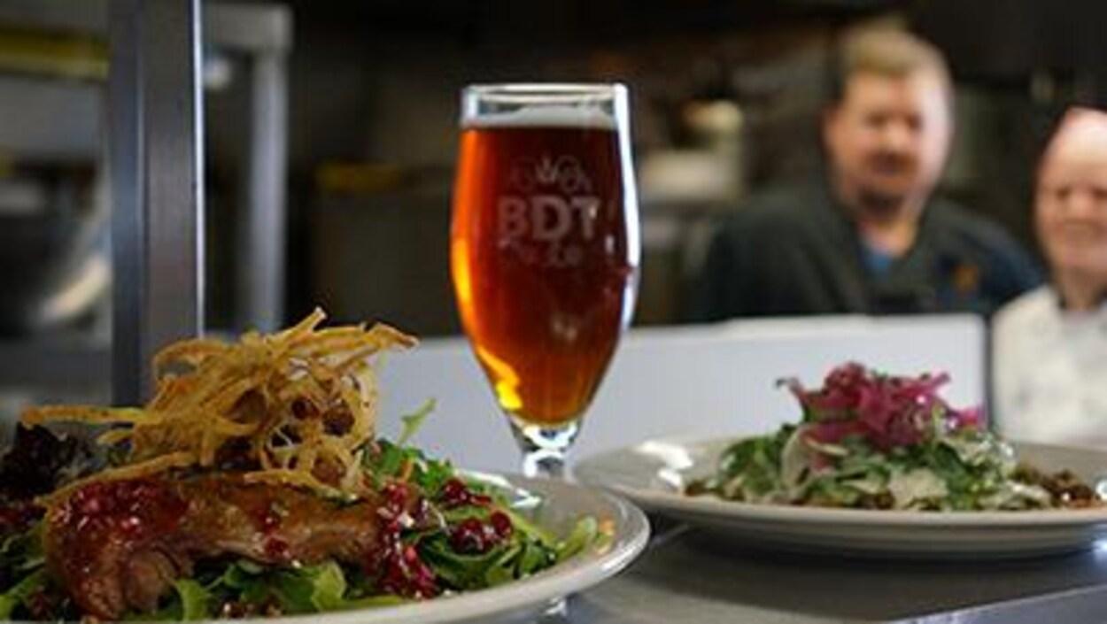 Un verre de bière et deux plats sont prêts à être servis à des clients de la microbrasserie