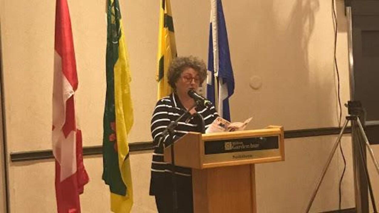 Une femme parle derrière un micro derrière quatre drapeaux.