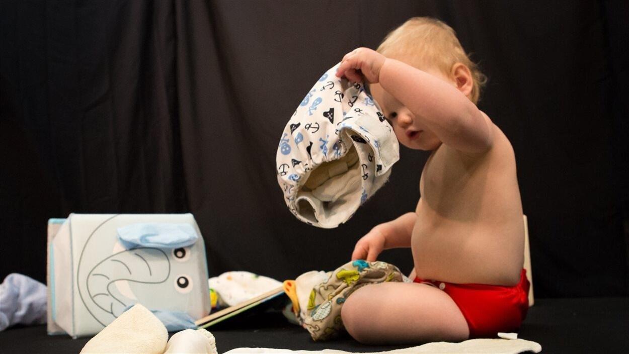 Un bébé tient une couche lavable.