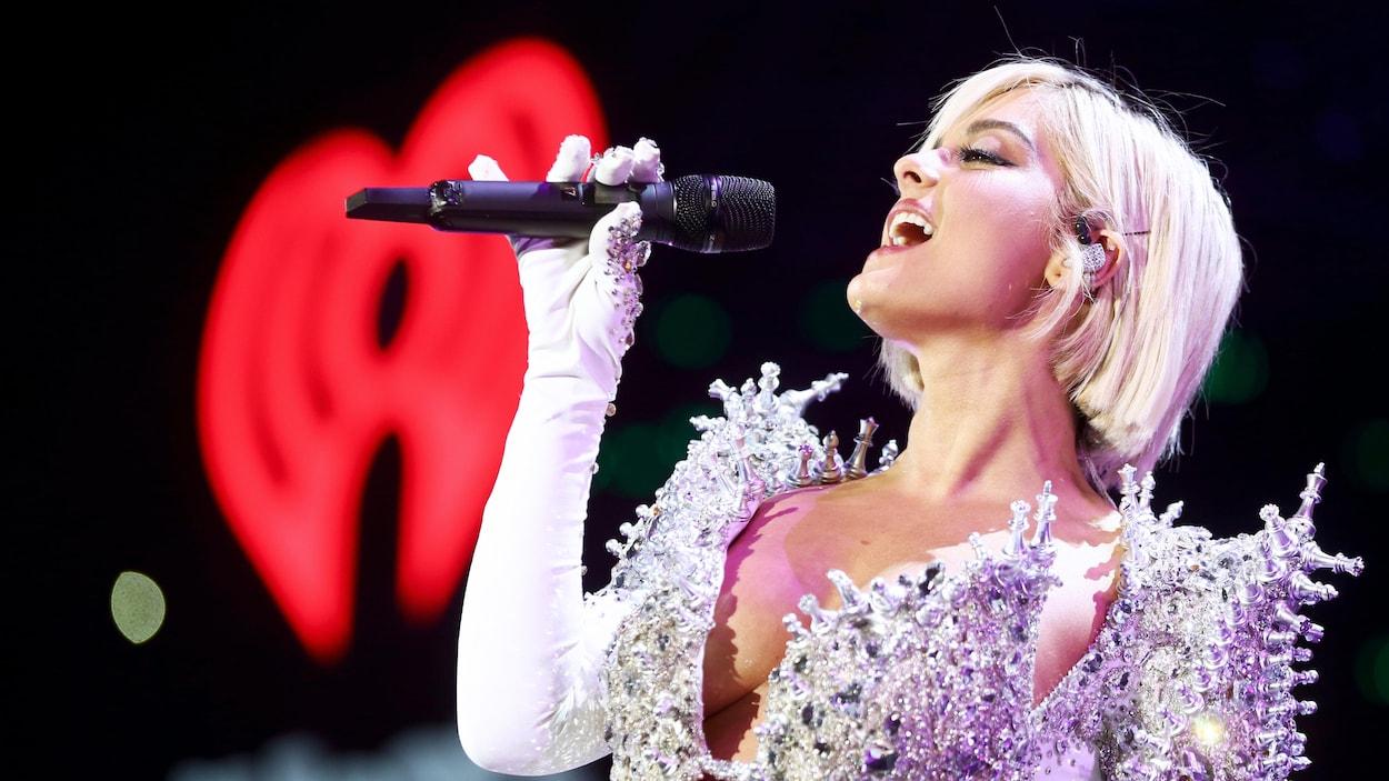 La chanteuse Bebe Rexha, qui porte une robe blanche scintillante ornée de pièces de jeu d'échecs, chante avec un micro à la main lors d'un concert.
