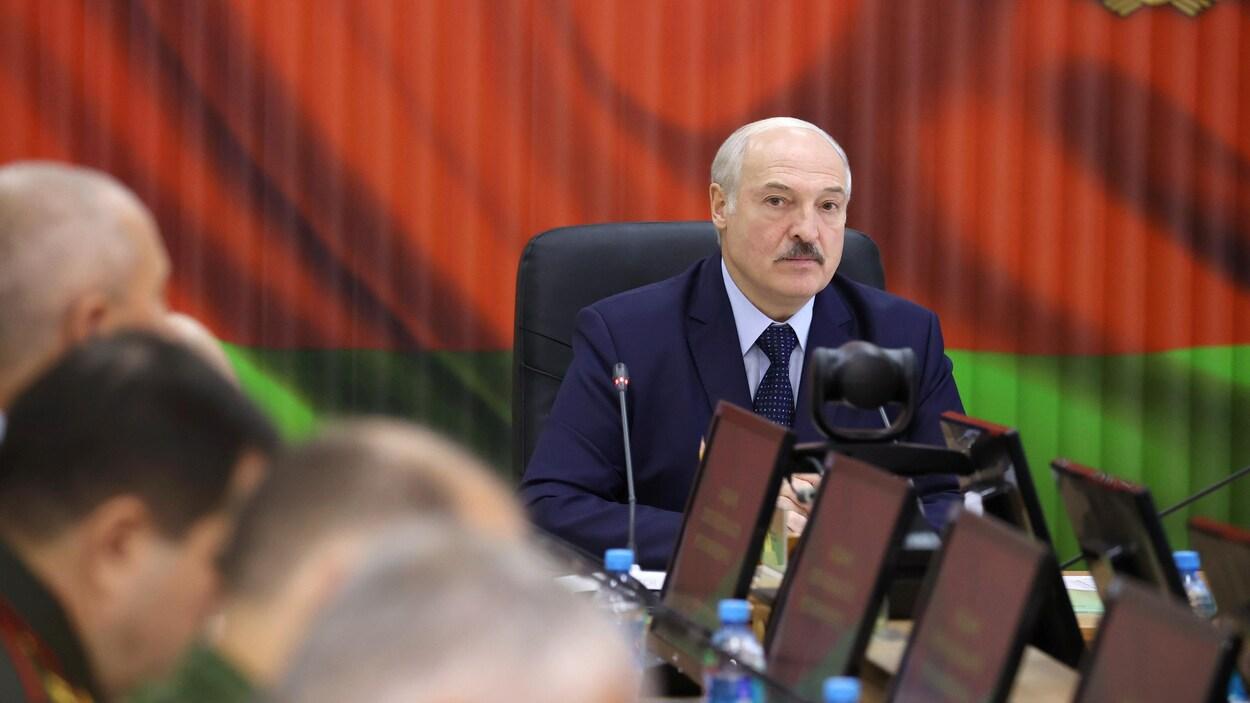 Le président du Bélarus assis dans une salle de conférence.