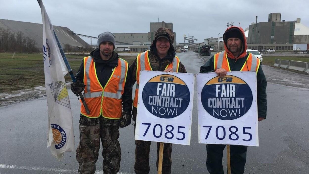Trois hommes portant des pancartes et un drapeau syndical devant l'usine.