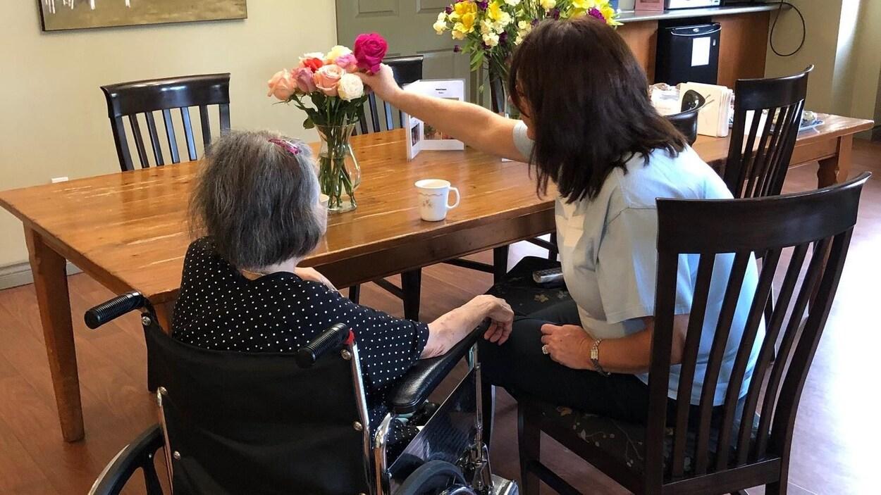 Une femme âgée en fauteuil roulant attablée à côté d'une femme qui prend une rose d'un vase posé sur la table.