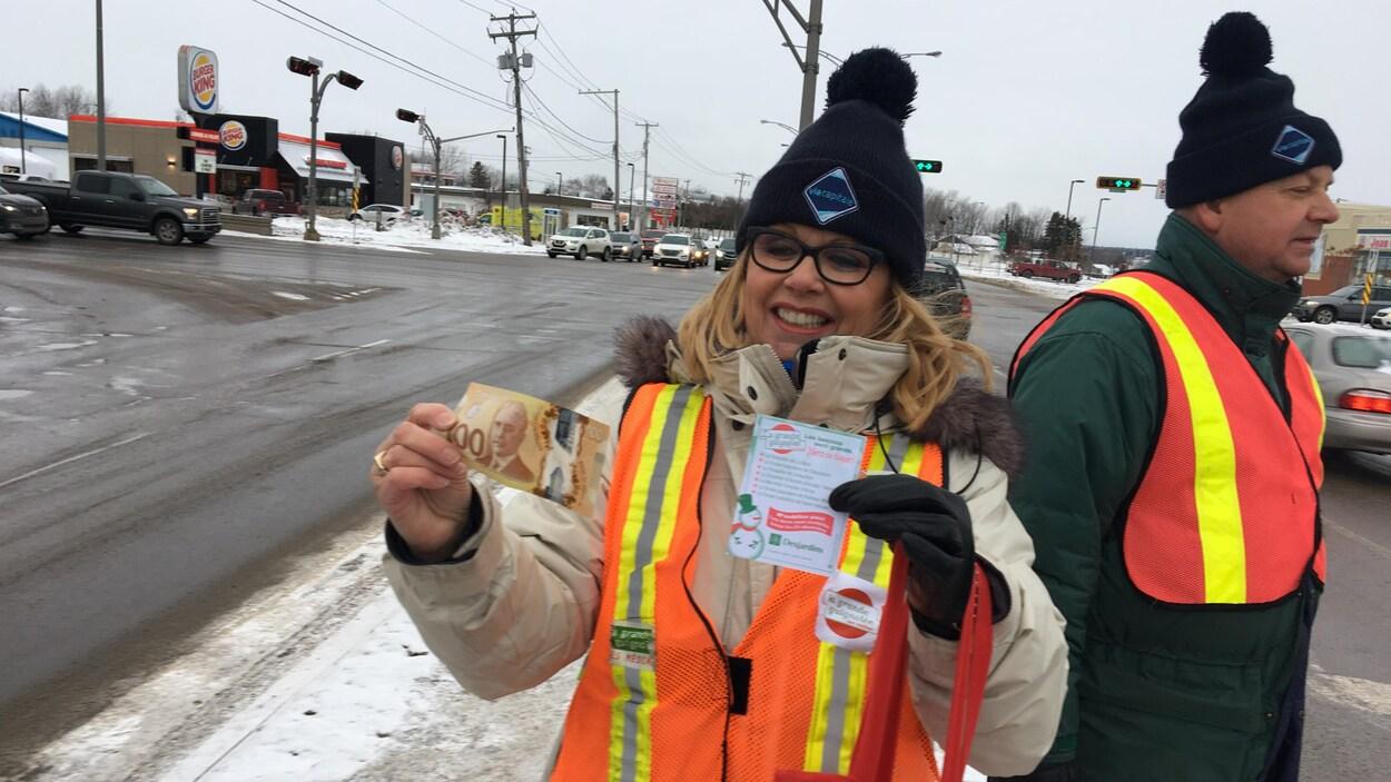 Une bénévole montre un billet de 100$ qu'elle a recueilli.