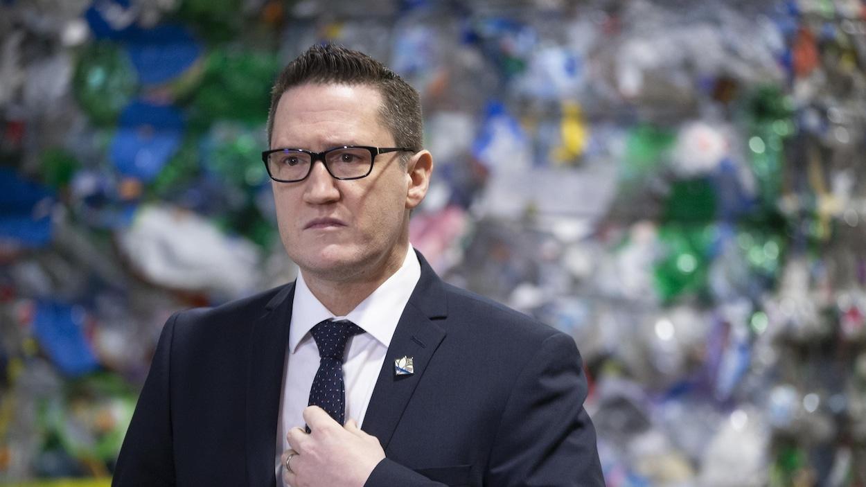 Benoit Charette devant des matières recyclables.