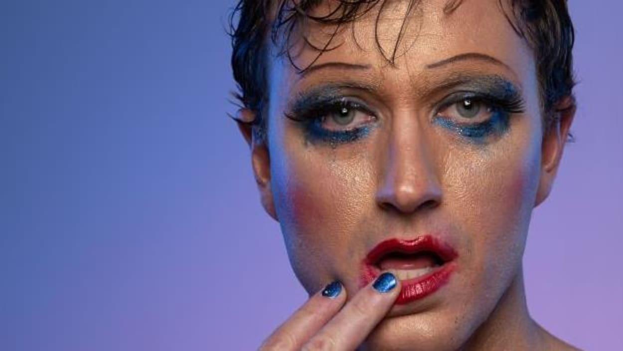 Un homme maquillé et transpirant dépose sa main droite sur sa lèvre inférieure.