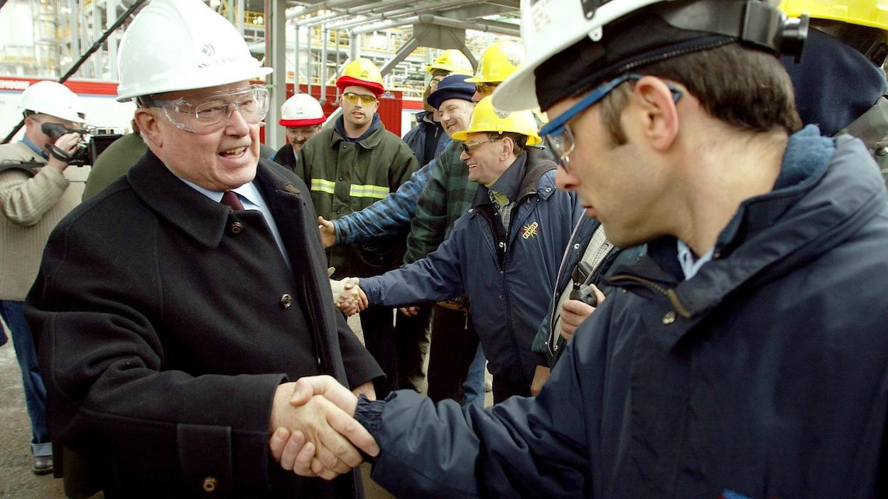 M. Landry, coiffé d'un casque de construction, serre la main d'un ouvrier en souriant.
