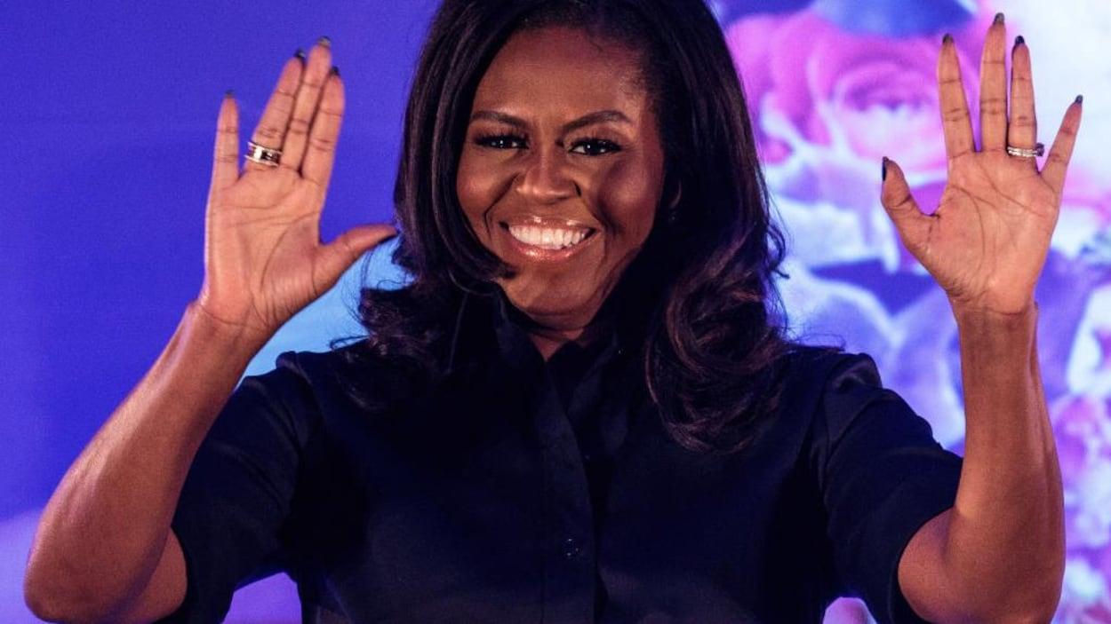 Michelle Obama, les deux mains en l'air.