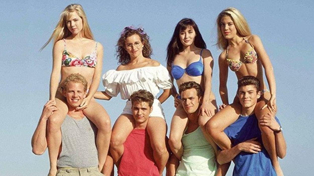 Les 8 personnages principaux de Beverly Hills, 90210 en photo sur la plage.