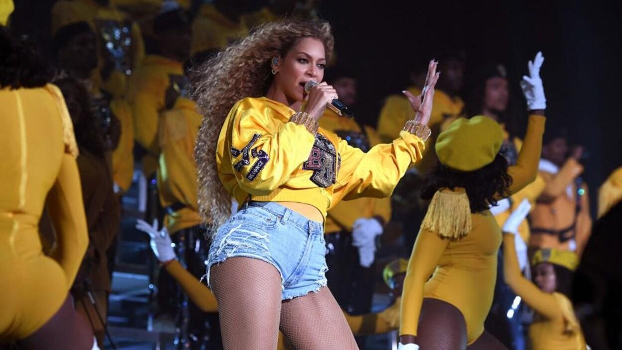 Beyoncé chante sur scène entourée de ses danseuses.