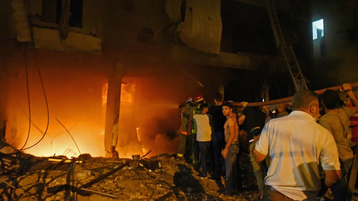 Des flammes sortent du rez-de-chaussée d'un édifice devant lequel s'affairent pompiers et volontaires.