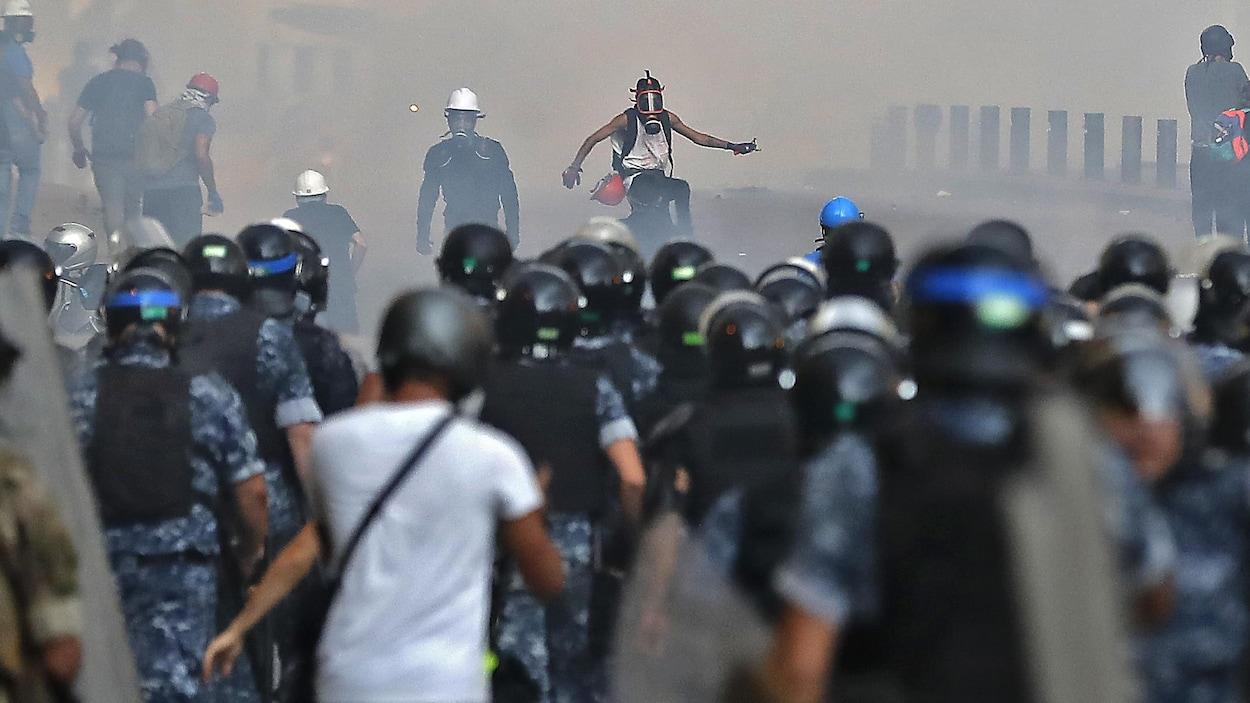 Quelques manifestants portant des masques à gaz défient des policiers en tenu anti-émeute.