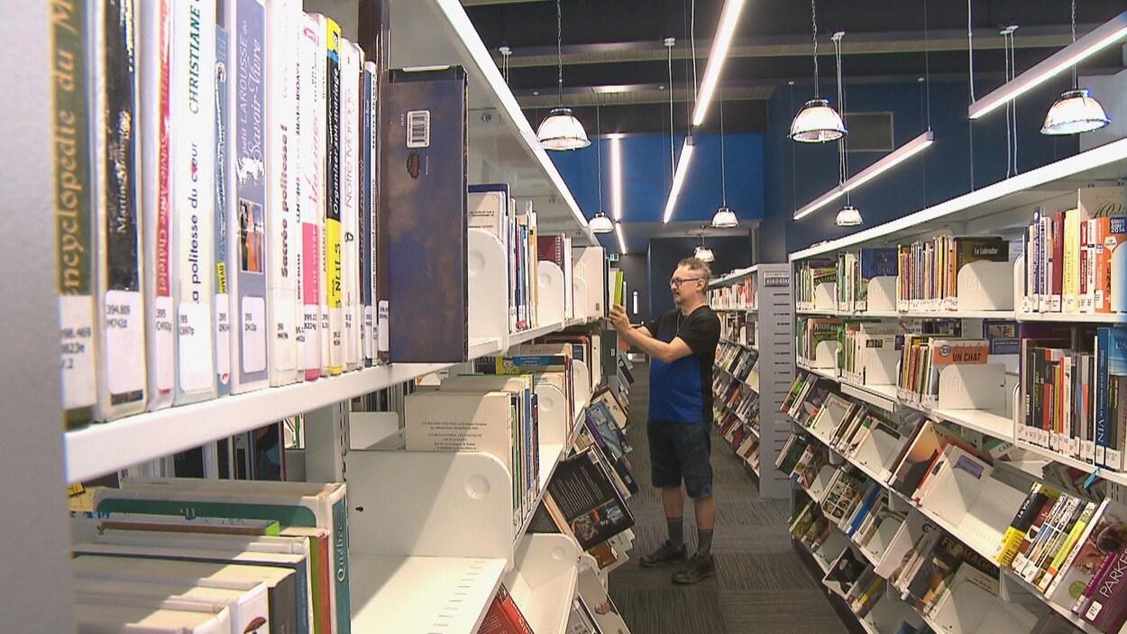 Un homme entre les rangées de livres