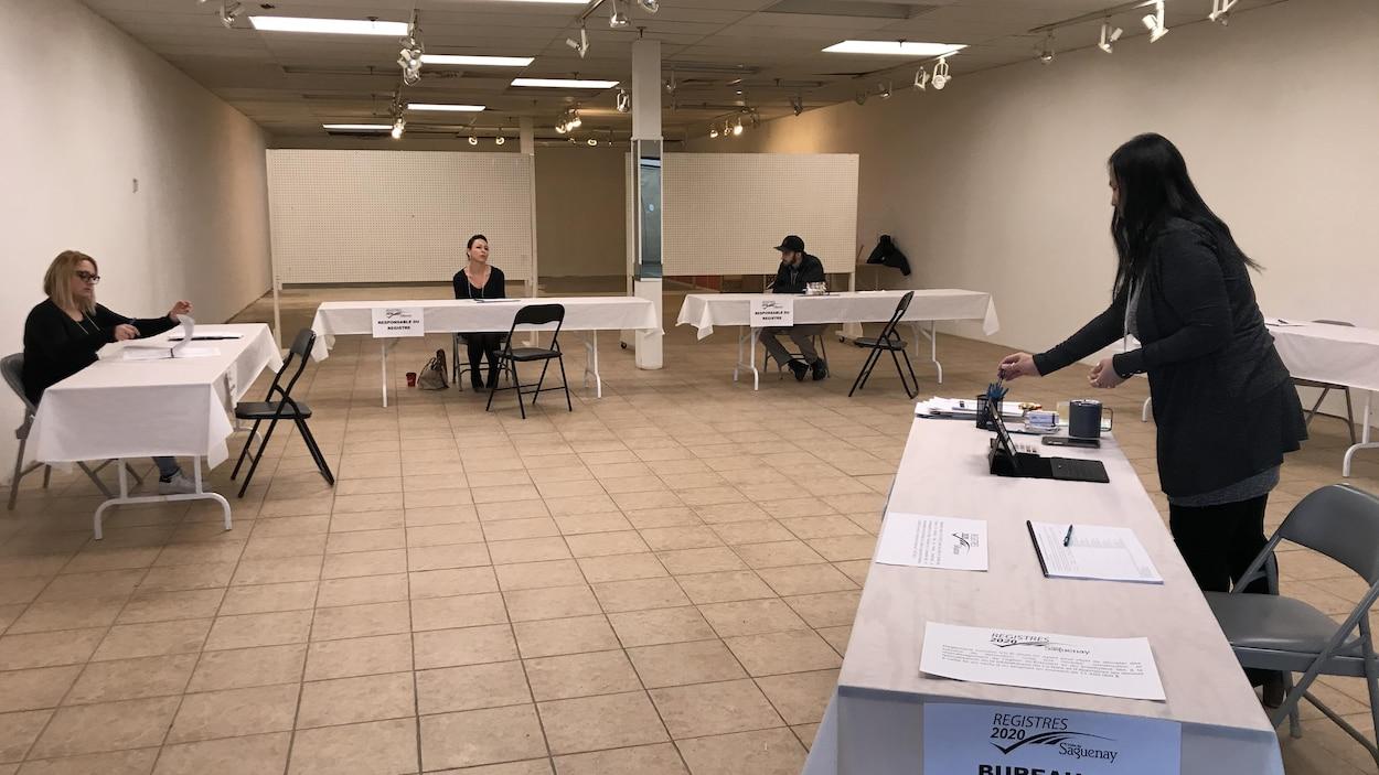 Trois personnes assises à trois tables dans une salle presque vide.