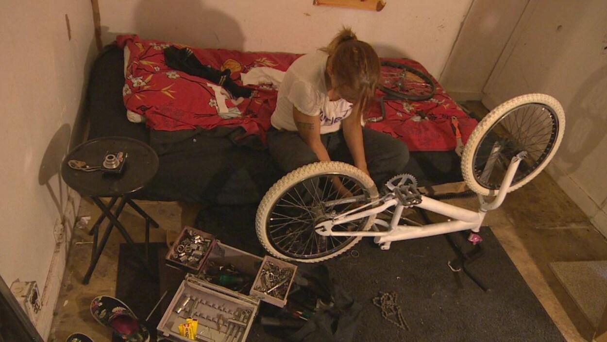 Un petite chambre avec un lit, une table, une boite à outil et un vélo. Une femme s'affaire à le réparer.