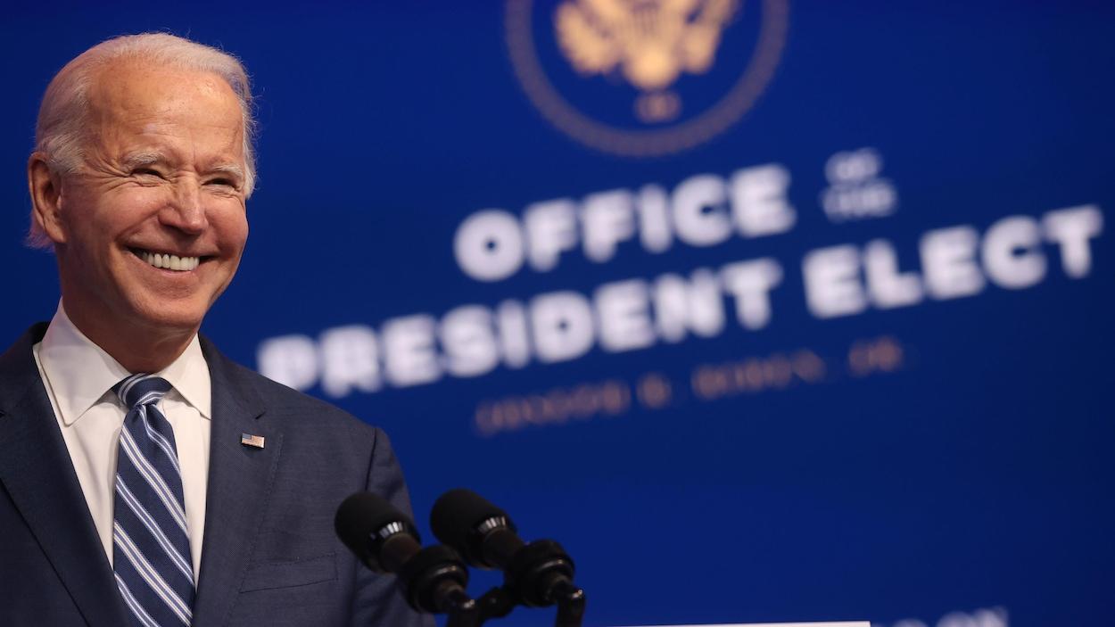 Portrait de Joe Biden qui sourit en conférence de presse.