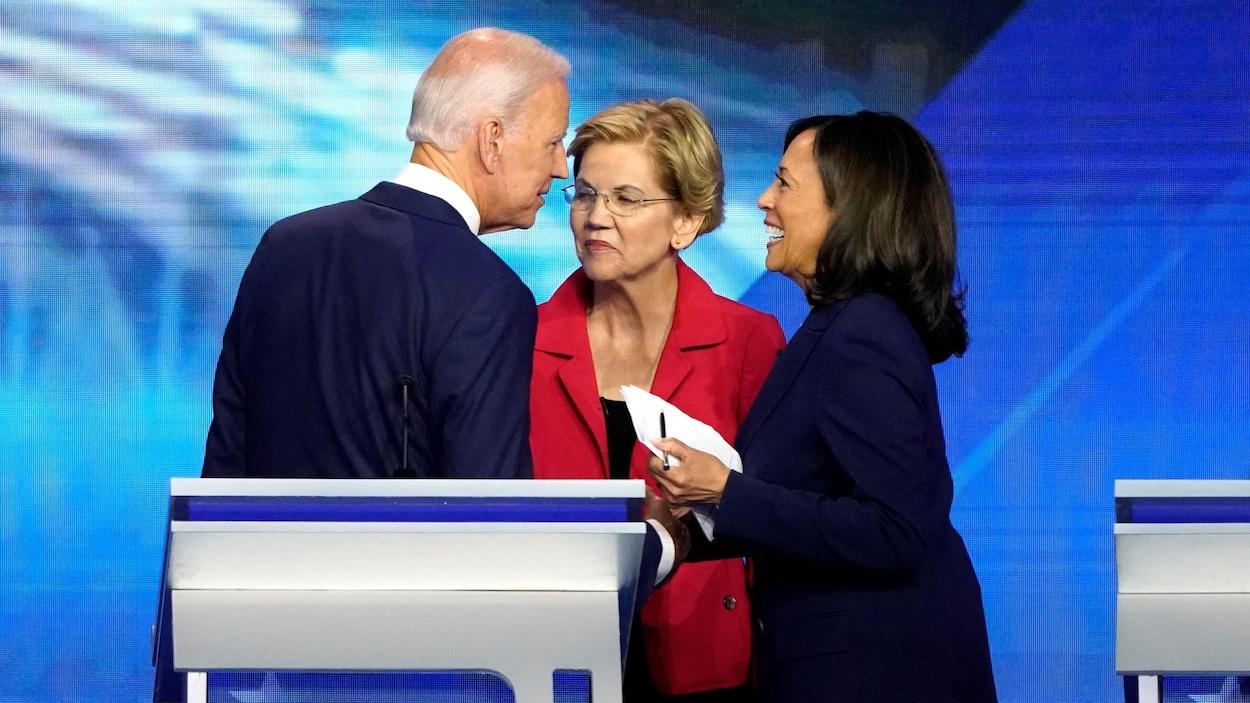Joe Biden, Elizabeth Warren et Kamala Harris discutent près des lutrins après un débat.