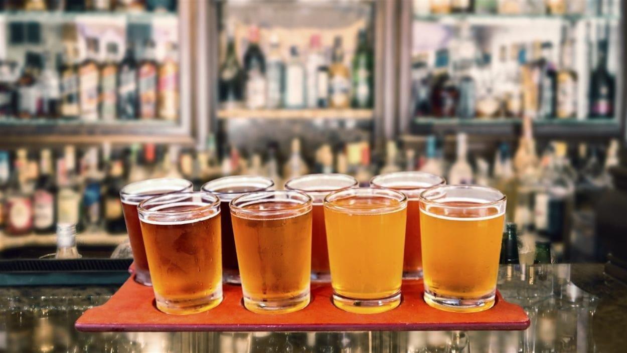 Des verres de bière disposés sur un plateau de dégustation.