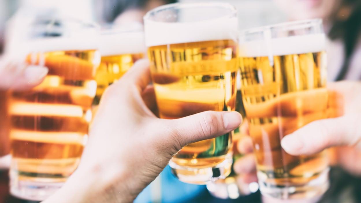Des personnes trinquent avec leur verre de bière.