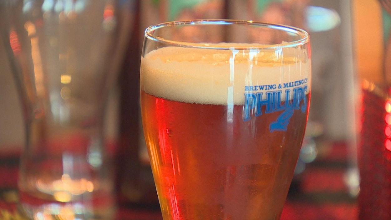 Un verre de bière avec un logo de la brasserie Phillips