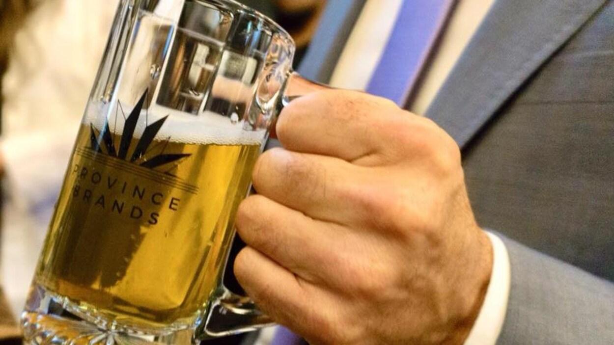 Une main tient un bock de bière de marque Province Brands of Canada.