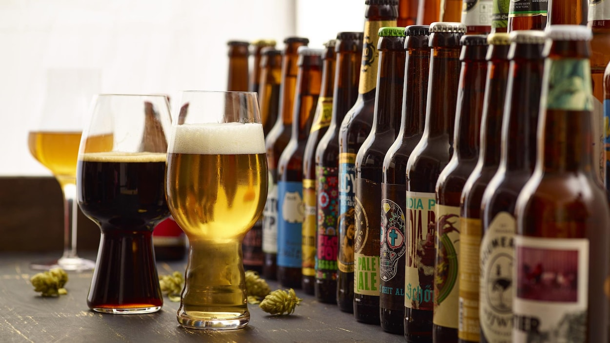 Plusieurs bouteilles de bières différentes et trois verres de bière remplis sont disposés sur une table.