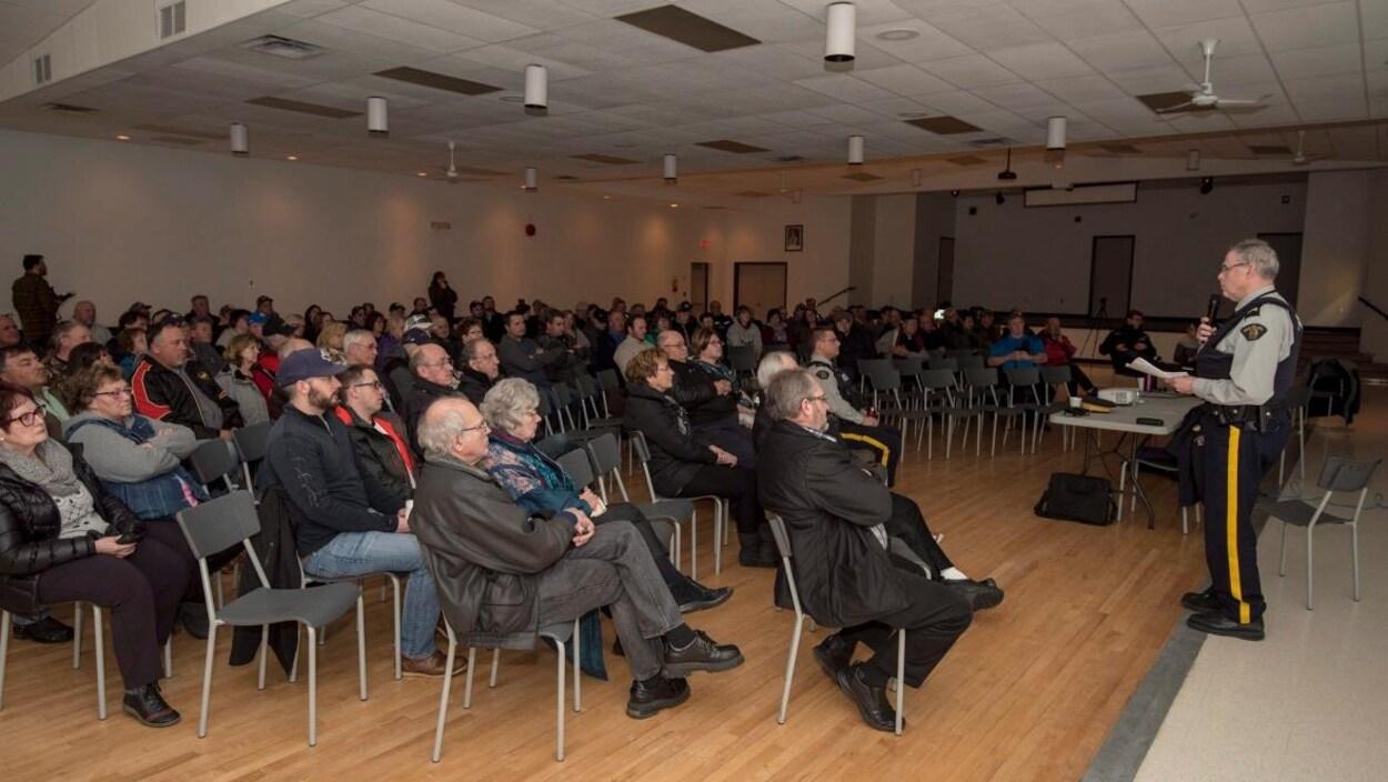 s'adresse aux participants présents à l'assemblée publique.