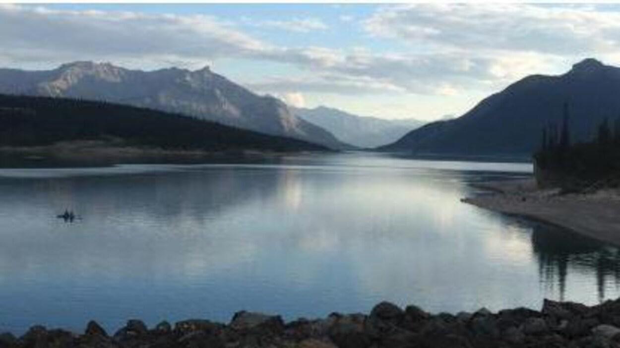 Vue sur un lac entouré de montagnes.