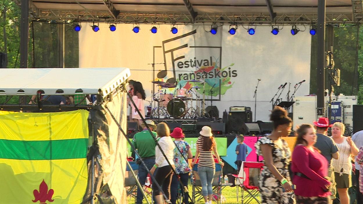 Scène du Festival fransaskois. De nombreuses personnes sont devant la scène où se trouvent des instruments de musique et des micros.