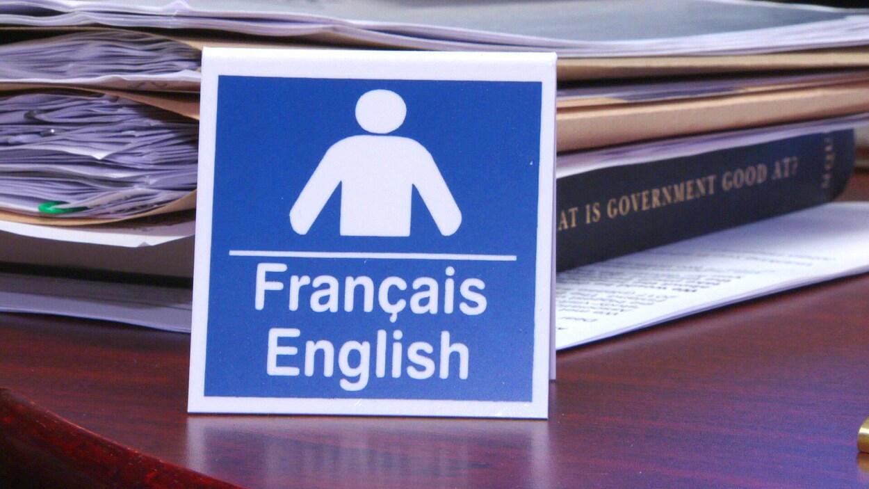 Affichette portant les mots « français » et « anglais » sur un comptoir.