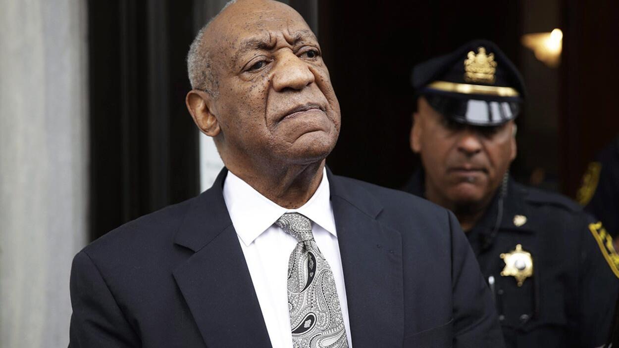 Bill Cosby se tenant debout devant un policier.