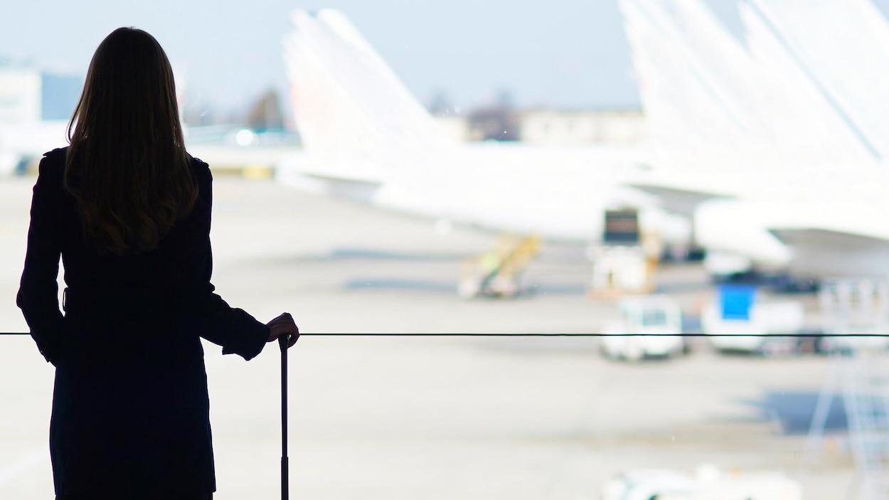 Une femme avec une valise roulante regarde des avions stationnés par la baie vitrée d'un terminal aéroportuaire.