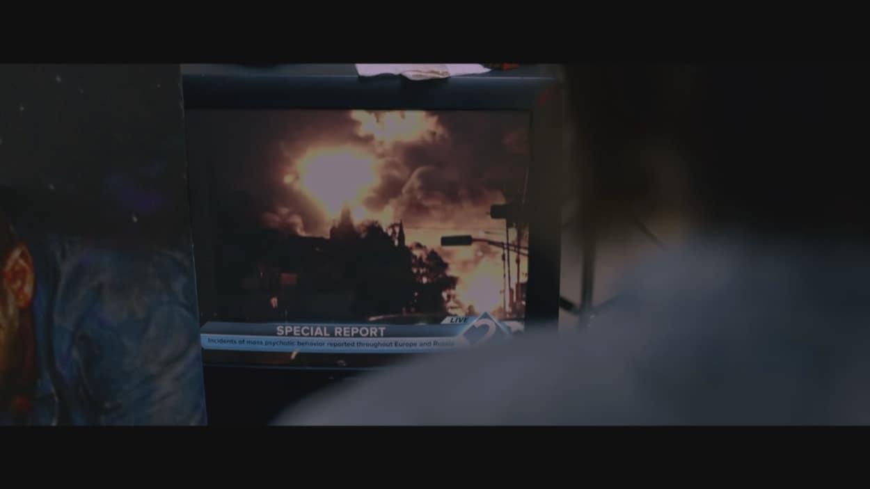 Une personne regarde un écran de télévision où une explosion se produit.