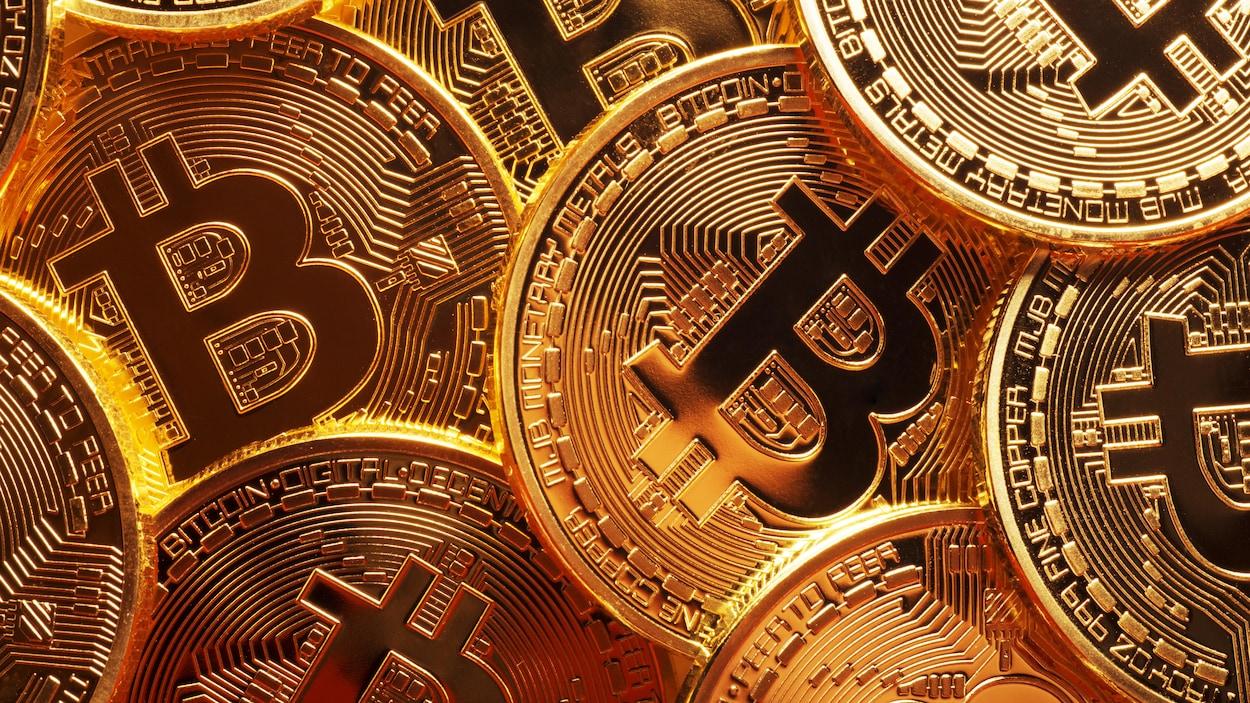 Une gros plan sur des pièces de monnaie dorées arborant le symbole de Bitcoin.