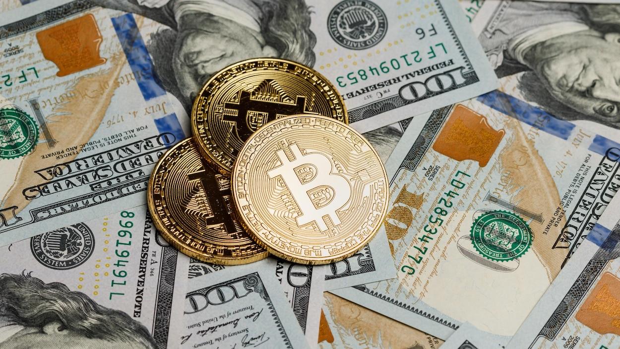 Des bitcoins sont déposés sur des billets de 100 dollars américains.