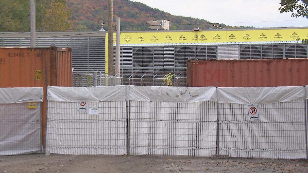 Les ventilateurs de Bitfarms cachés en partie par des conteneurs.
