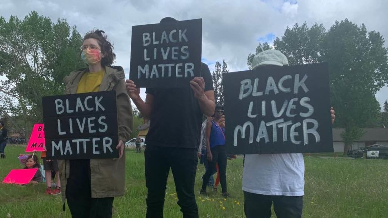 Trois personnes tiennent des affiches sur lesquelles on peut lire en anglais : Black Lives Matter.