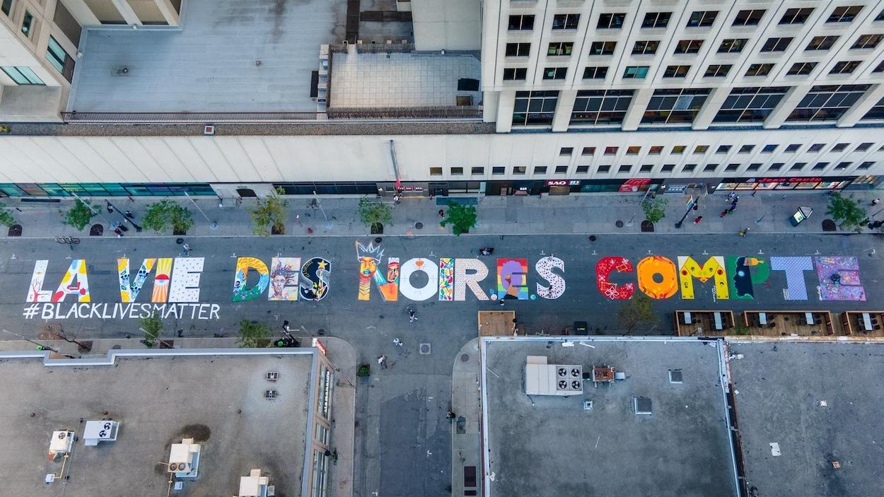 Vue des airs, une fresque, peinte sur le sol de la rue Sainte-Catherine à Montréal, une fresque indiquant « La vie des Noir.e.s compte », avec la mention #BlackLivesMatter.