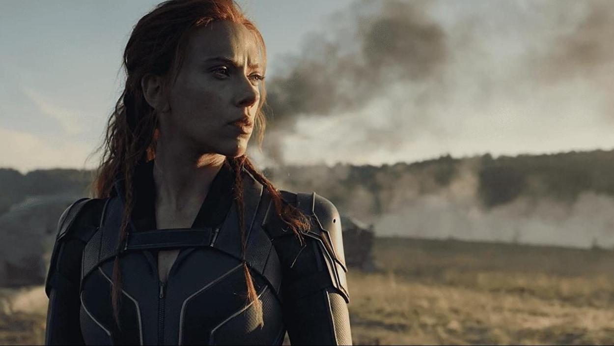 Une femme vêtue d'un costume de superhéroïne observe l'horizon. Un panache de fumée noire est visible à l'arrière-plan.