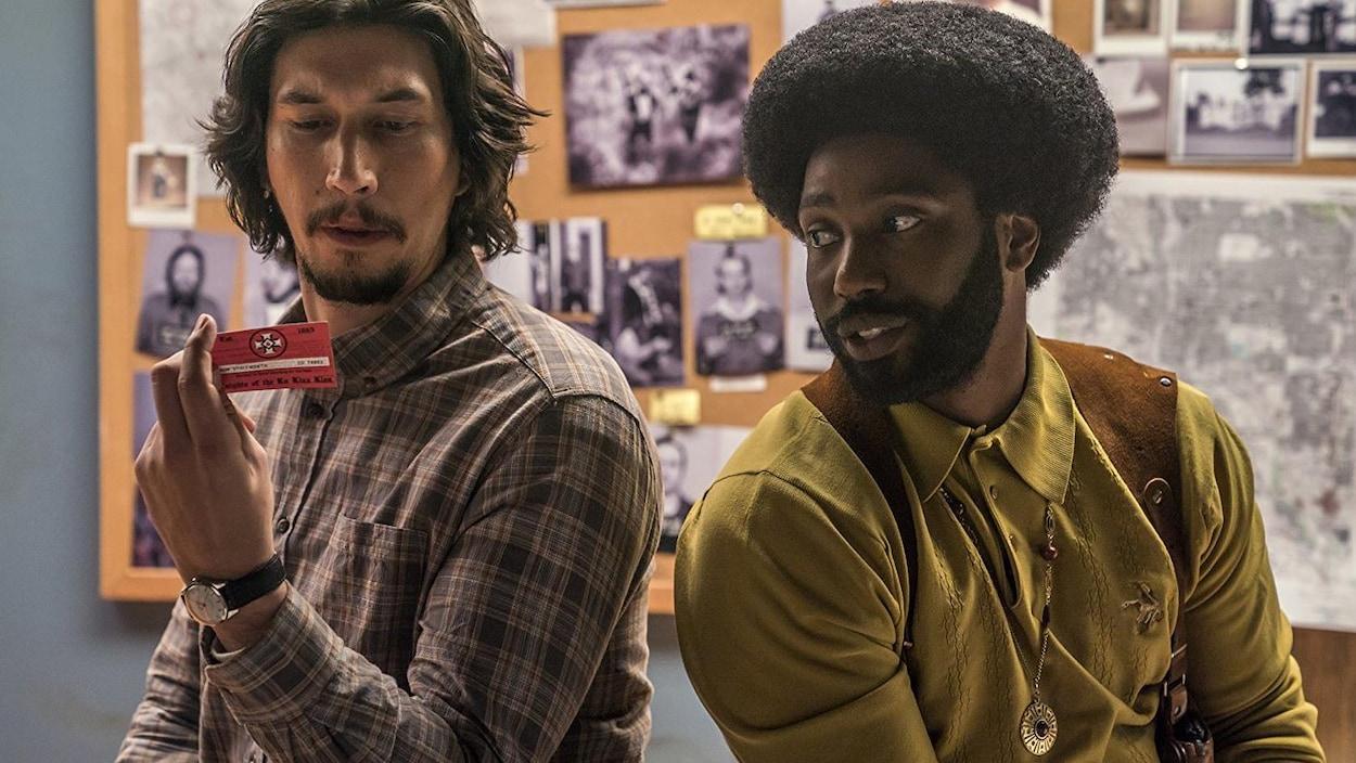 Adam Driver et John David Washington regardent une carte de visite dans une scène du film «Opération infiltration<».