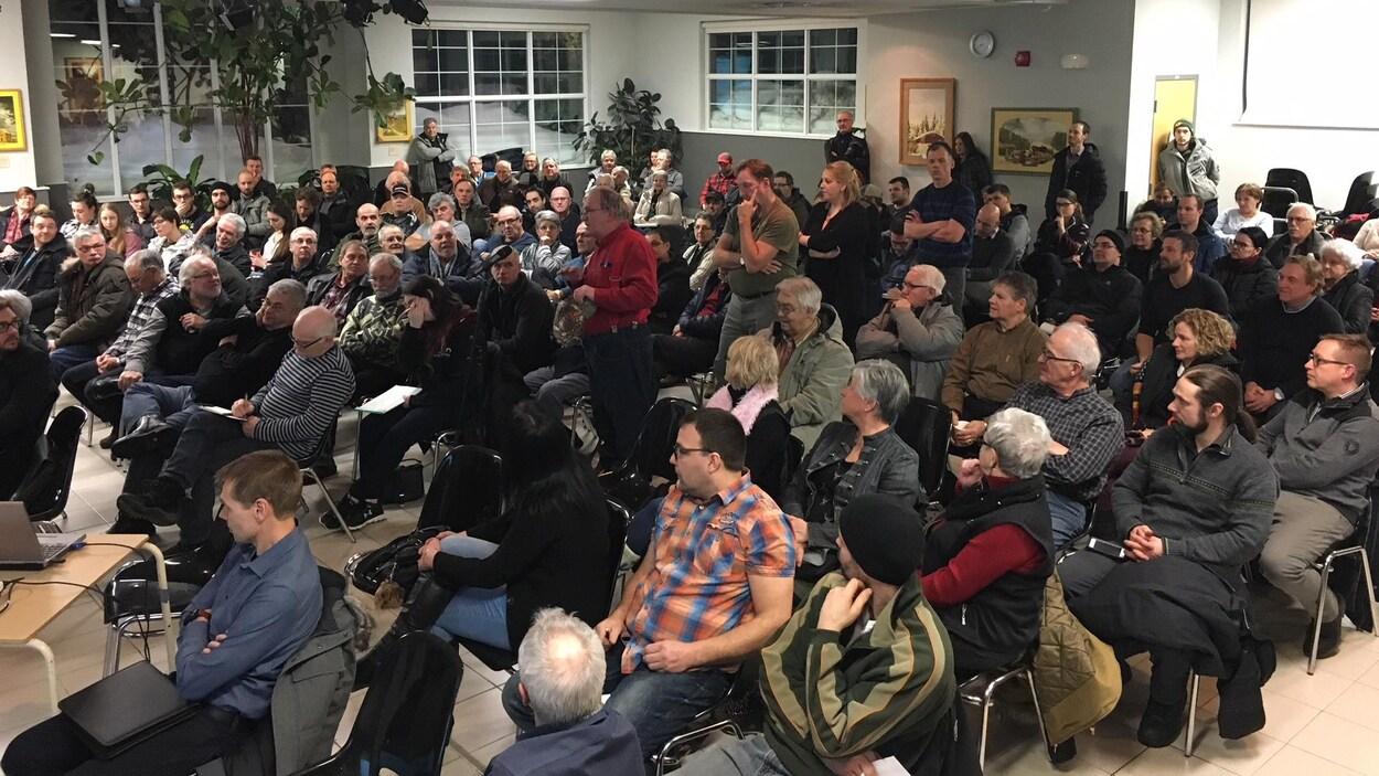 Une salle communautaire est remplie de citoyens.