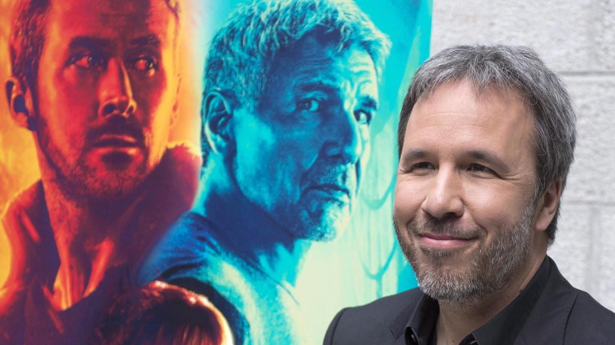 Denis Villeneuve sourit devant l'affiche du film « Blade Runner 2049 »