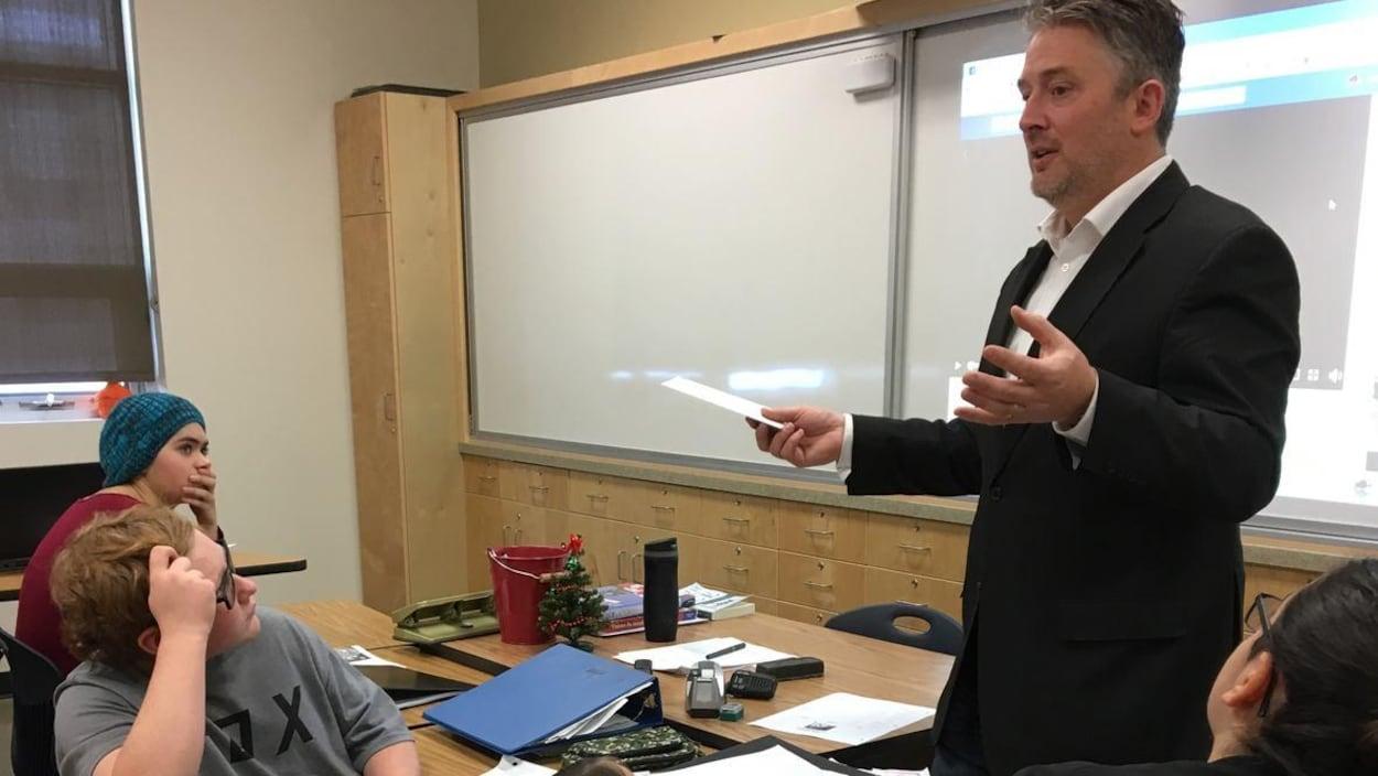Vue sur un homme avec veston debout devant une classe d'élèves.