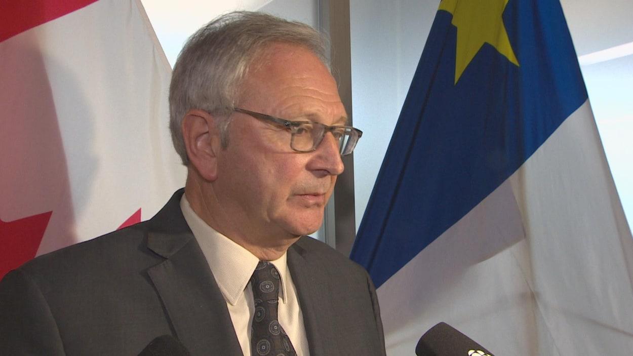 Blaine Higgs devant un micro et le drapeau du Canada et de l'Acadie.