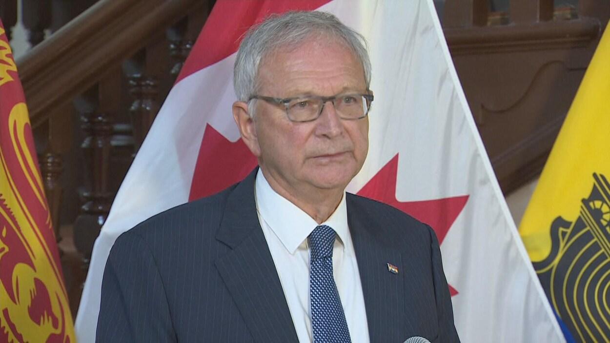Blaine Higgs en conférence de presse devant des drapeaux du Canada et du Nouveau-Brunswick.
