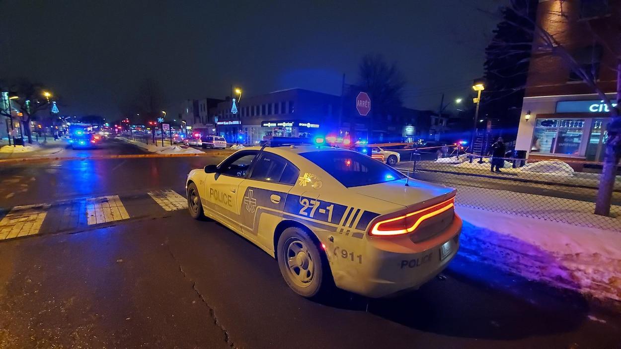 Une voiture du SPVM est immobilisée à côté d'un périmètre de sécurité sur un boulevard.