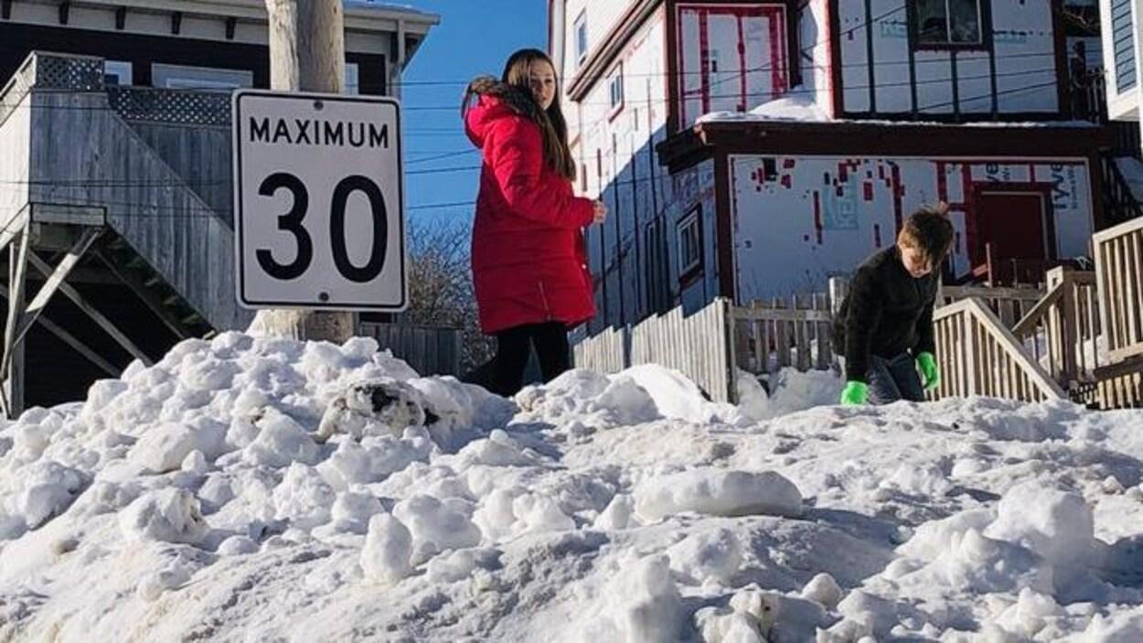 Deux enfants jouent au sommet d'un banc de neige à la même hauteur qu'un panneau de signalisation routière.