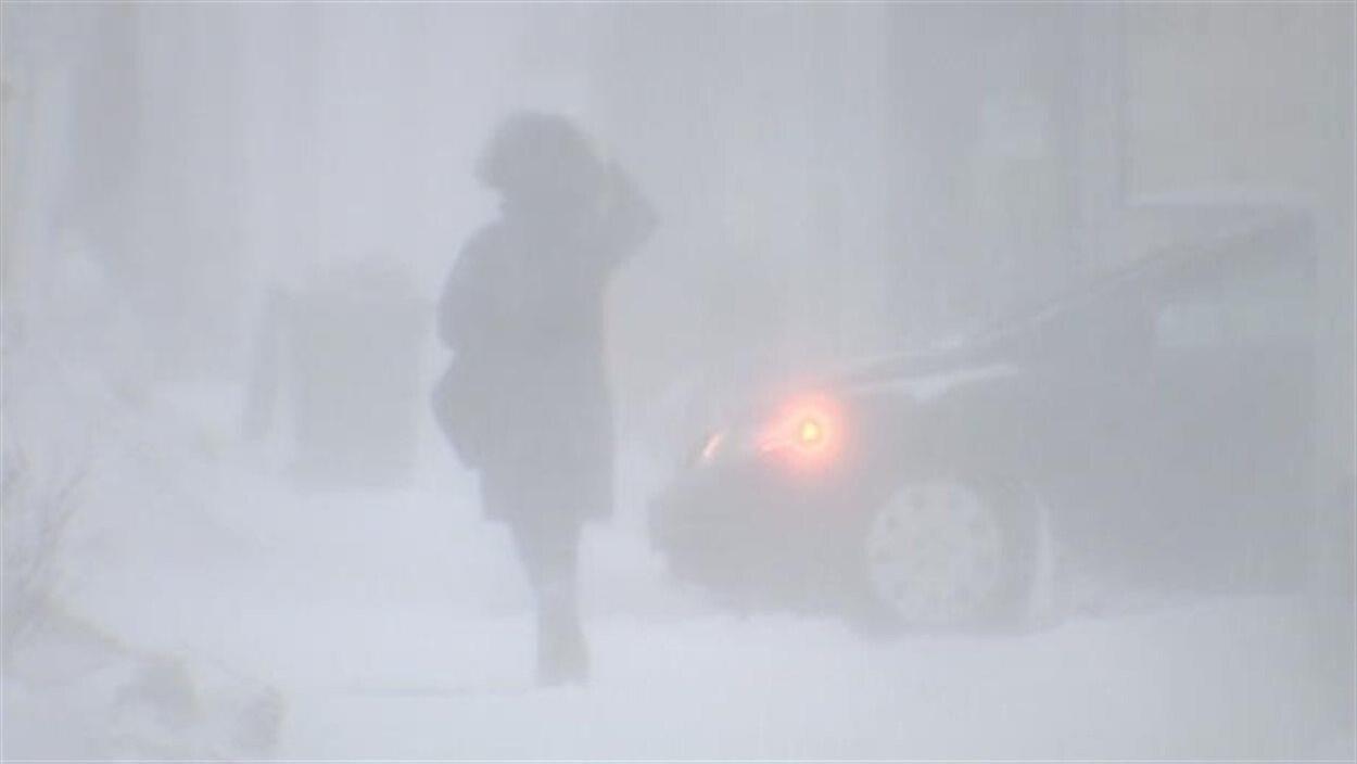 Une dame marche sur un trottoir dans la poudrerie.