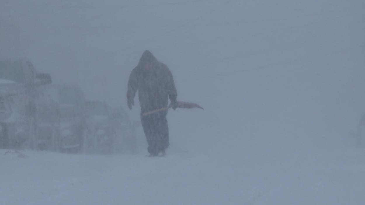 Un homme avec une pelle dans un blizzard.